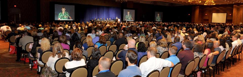 Image of audience listening to conference speaker